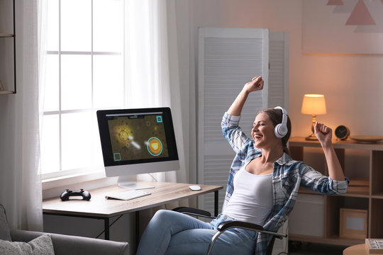 Emotional young woman playing video games at home