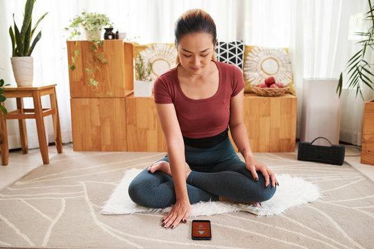 Woman setting app for meditation