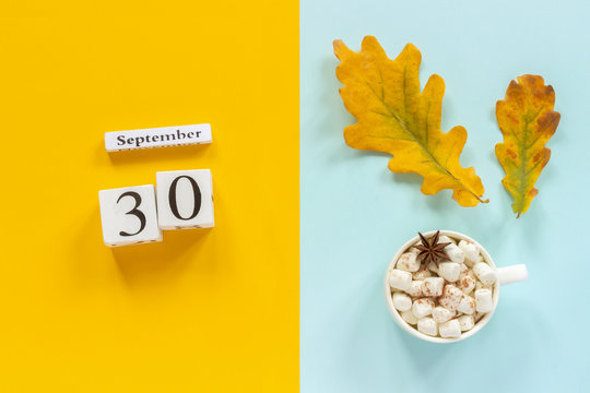 Autumn composition. Wooden calendar September 30, cup of cocoa with marshmallows and yellow autumn leaves on yellow blue background. Top view Flat lay Mockup Concept Hello September.