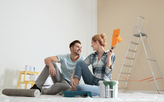 Happy couple with paint planning home repair indoors