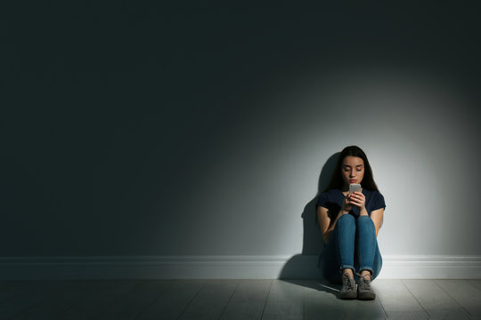 Lonely woman with smart phone sitting on floor in dark room. Space for text