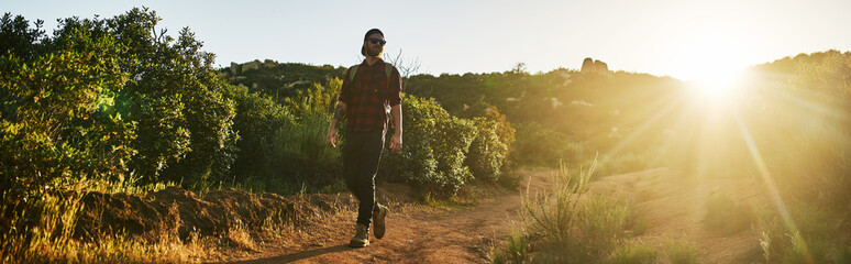bearded millennial hiker walking trail with backpack during sunset