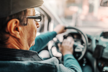 Caucasian senior man with cap on head and eyeglasses driving his car. Picture taken from the backseat.
