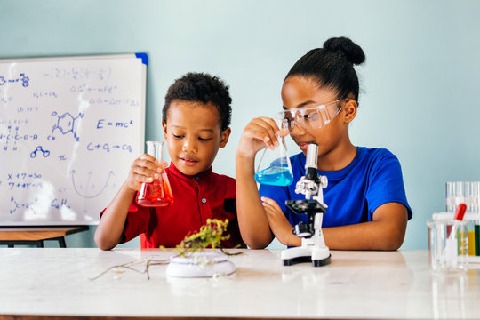 Cheerful black pretty smart children in casual clothes sitting in school chemistry laboratory and holding flasks with colourful liquids