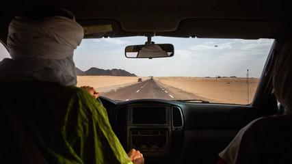 Tuareg man driving on his car through Sahara Desert