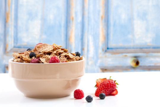 A bowl of muesli breakfast cereal and milk with berries on a blue rustic woodbackground