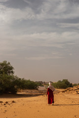 A muslim girl with hijab walking under the sun in Sahara, Algeria