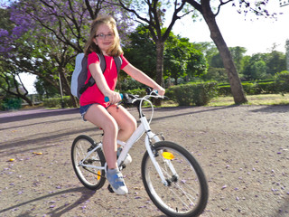 Happy girl on bicycle on her way to the school