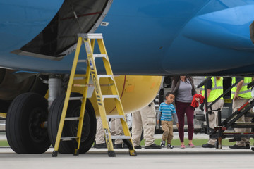 Law enforcement officials move migrant families in federal custody from buses to a chartered plane scheduled to fly to San Diego at Brownsville South Padre International Airport in Brownsville