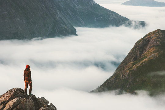 Traveler on cliff overlooking mountain clouds alone hiking adventure journey outdoor Norway vacations traveling lifestyle weekend getaway