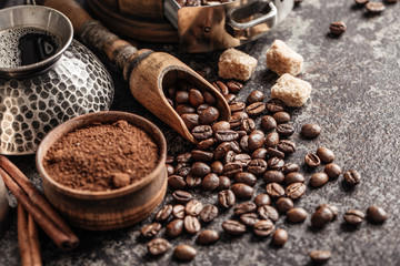 Fototapete - Coffee beans in wooden spoon on dark textured background.