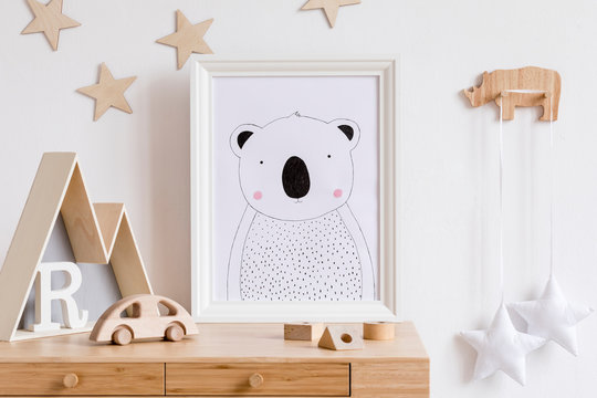 Stylish scandi childroom with white mock up photo frame, wooden accessories, toys, mountain box and stars pattern on the background wall. Bright and sunny interior. Template, Real photo. Wooden desk.