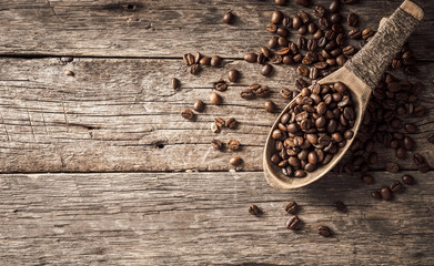 Wall Mural - Coffee beans in wooden spoon on wood background.