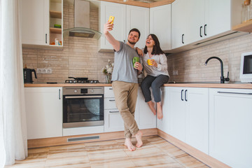 cheerful man with woman taking selfie on the kitchen while drinking tea