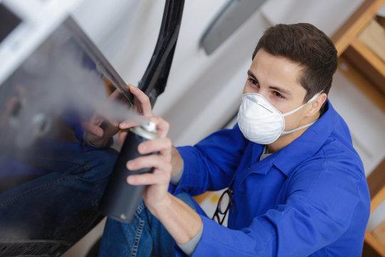young mechanic respraying car panel
