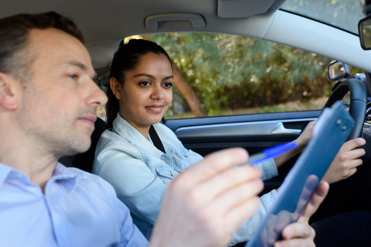 young woman having driving lesson in car