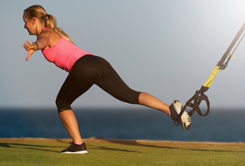Fitness young woman engaged in morning exercises on the beach during sunrise, lunge back
