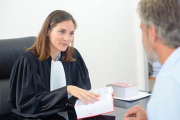 female lawyer holding book in meeting with male client