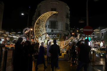 People take pictures of an illuminated crescent, a decoration made for the holy fasting month of Ramadan in Amman