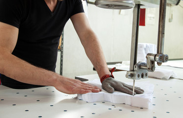 Worker using a machine in factory with iron glove
