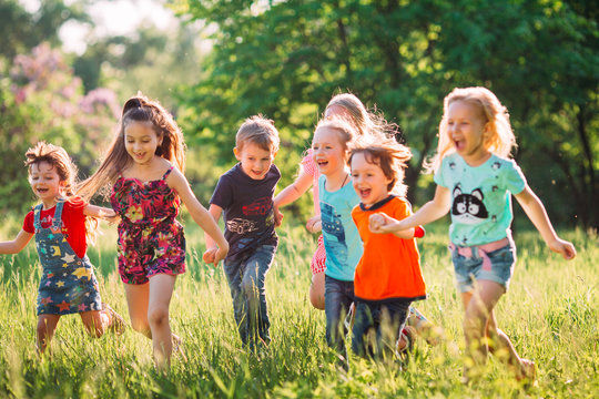 Large group of kids, friends boys and girls running in the park on sunny summer day in casual clothes .
