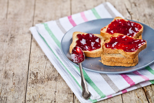 Fresh toasted cereal bread slices with homemade cherry jam and spoon on ceramic plate closeup on linen napkin on rustic wooden table background.