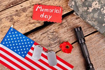 Veteran's accessories on wood. American flag, dog tags, red poppy and torch. Attributes for memorial day.
