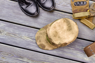 Military cap, gloves and boots. Top view. Wooden desk background.