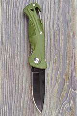 Green pocketknife on wood. Close up, wooden background.