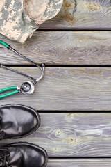 Camouflage jacket, stethoscope and black shiny shoes. Wooden desk background.