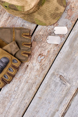 Military fingerless gloves, cap and dog tags. Top view, flat lay. Wooden desk background.