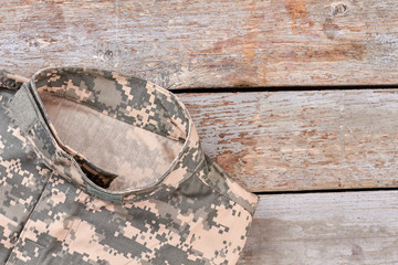 Camouflage military jacket, close up. Wooden desk surface background.