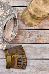 Military clothes, fingerless gloves and cap, close up. Wooden desk background.