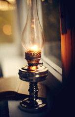 Vintage kerosene lamp stands on a white windowsill