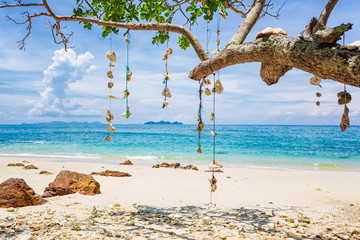 Empty dream Beach with white sand on the island of Koh Ngai, Thailand. Shells hanging from a tree branch on a string. Wall mural