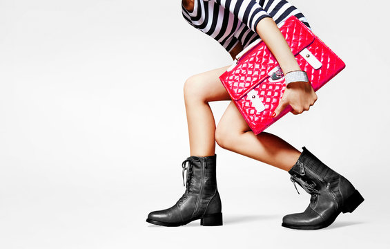 Woman with red bag and black short boots on white background