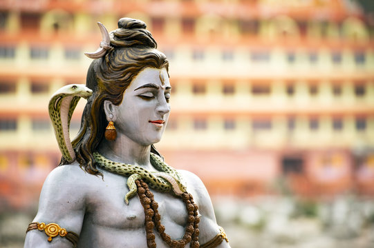 Stunning view of the statue of sitting Lord Shiva on the riverbank of the Ganges river. Blurred Trimbakeshwar Temple in the background. Rishikesh, Uttarakhand, India.