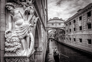 Fototapete - Venice cityscape with old sculpture in black and white, Italy. Tourist gondolas sail under famous Bridge of Sighs. It is a landmark of Venice. Romantic water trip on a narrow canal across Venice.