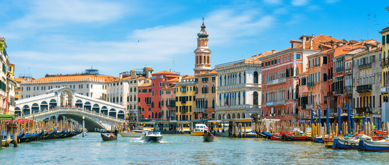 Wall Mural - Rialto Bridge over Grand Canal, Venice, Italy. It is a famous landmark of Venice. Panorama of the old Venice city in summer. Cityscape of Venice with colorful houses and tourist boats on sunny day.