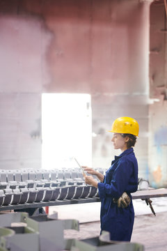 Side view portrait of female worker holding digital tablet while supervising production at plant, copy space