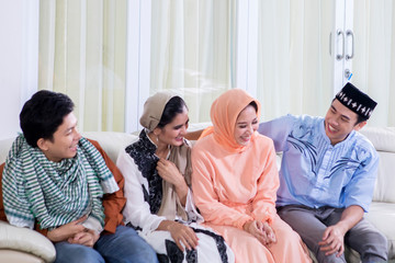 Happy Muslim people talk each other on the couch