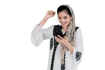 Happy Muslim woman with smartphone on studio