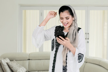 Muslim woman uses a phone with expressing happy