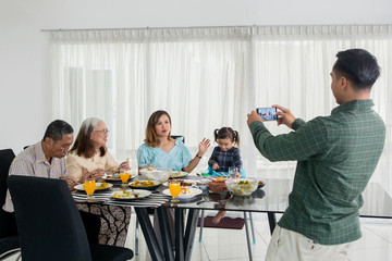 Young man takes photo his family in dining table
