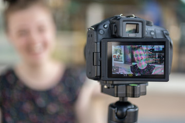 A caucasian young girl making a video blog (vlog) behind the camera