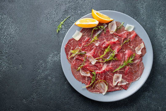 Marbled beef carpaccio with arugula, lemon and parmesan cheese on dark concrete table. Top view, flat lay with copy space