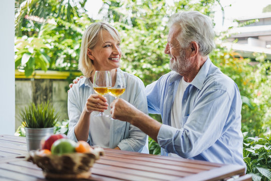 Senior couple enjoy drinking and clinking glass of wine to relax at home, senior retirement concept