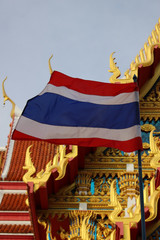 The Thailand national flag flies in front of a traditional Buddhist temple building and blue sky background.