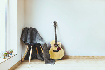 Contemporary home interior. Black chair covered with woolen gray blanket and acoustic guitar in front of an empty white wall. Succulent plants on the window.