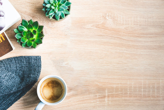 Top view of cosy home scene. Books, woolen blanket, cup of coffee and succulent plants over wooden background. Copy space.